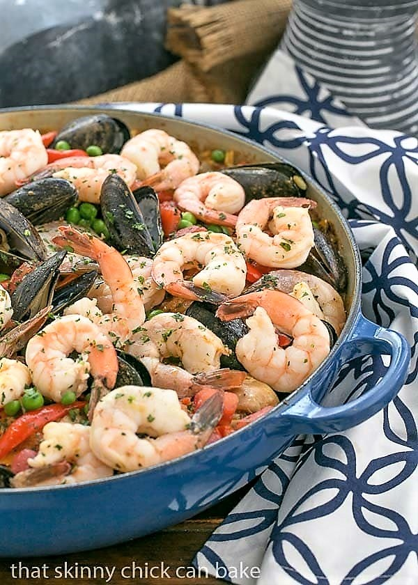 Julia Child's Paella a l'Americaine in a cast iron paella dish on a blue and white napkin