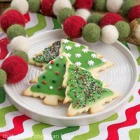 Frosted, sprinkled Christmas sugar cookies on a round white plate