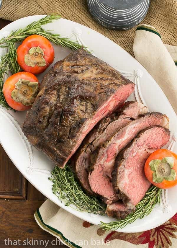 Overhead view of a Classic Prime Rib, partially sliced, garnished with fresh herbs and fruit