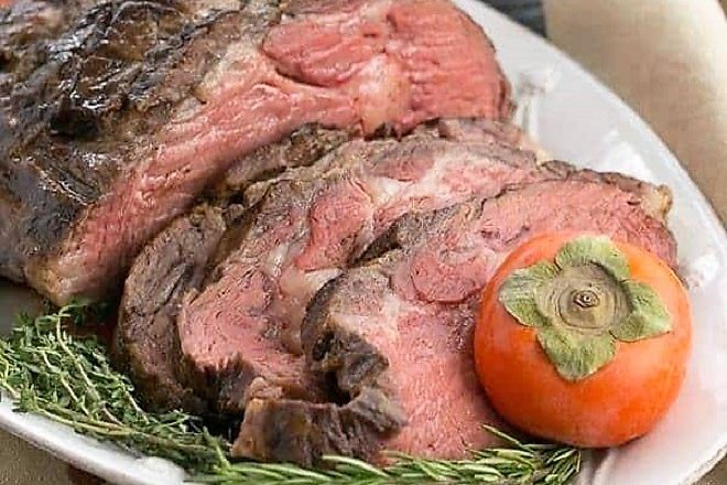Classic Prime Rib slices next to the roast on a white platter with rosemary and persimmon garnishes