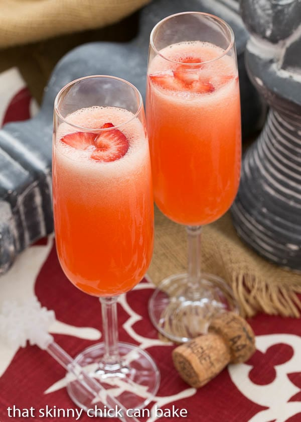 Peach Bellini cocktails in flutes with fresh strawberry slices