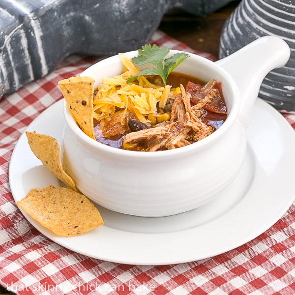 Slow Cooker Chicken Enchilada Soup in a soup bowl on a white plate