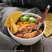 Enchilada soup in a white bowl with tortilla chips to garnish and a red handle spoon