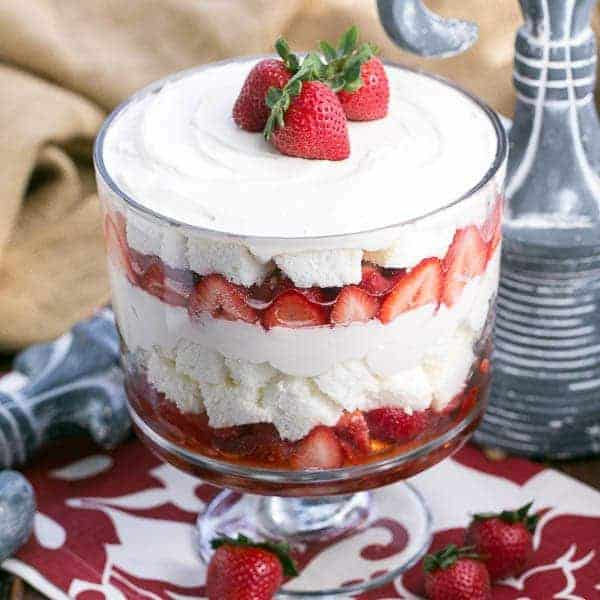 Strawberry Cheesecake Trifle | Layers of angel food cake, boozy berries and cream cheese filling