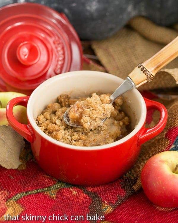 Apple Pear Crisp in a red ramekin with a bamboo handle spoon