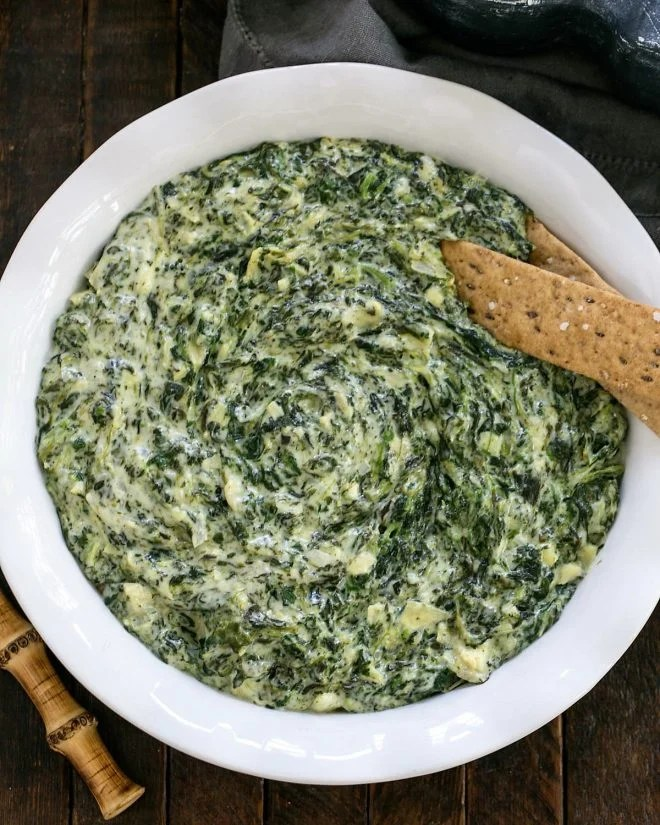 Overhead view of a white casserole dish of warm Spinach Dip Recipe