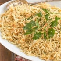 Spaetzel topped with parsley sprig on a white platter