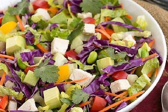 A vibrant Thai salad with a peanut dressing in a white serving bowl