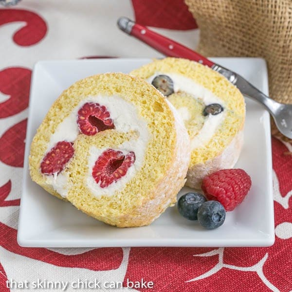 Slices of Berry Roulade on a square white plate with fresh berries to garnish