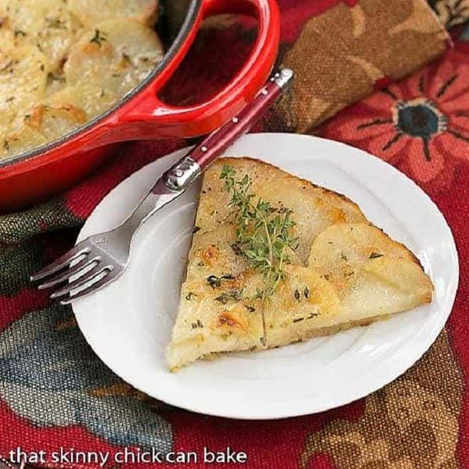 Slice of Cheesy Potato Galette on a white plate with a red handled fork