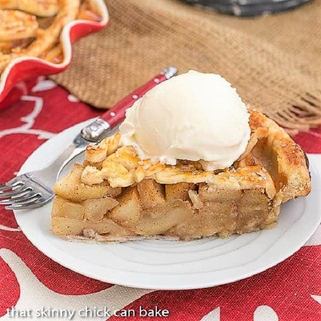 Leaf Topped Apple Pie slice on a white plate topped with vanilla ice cream