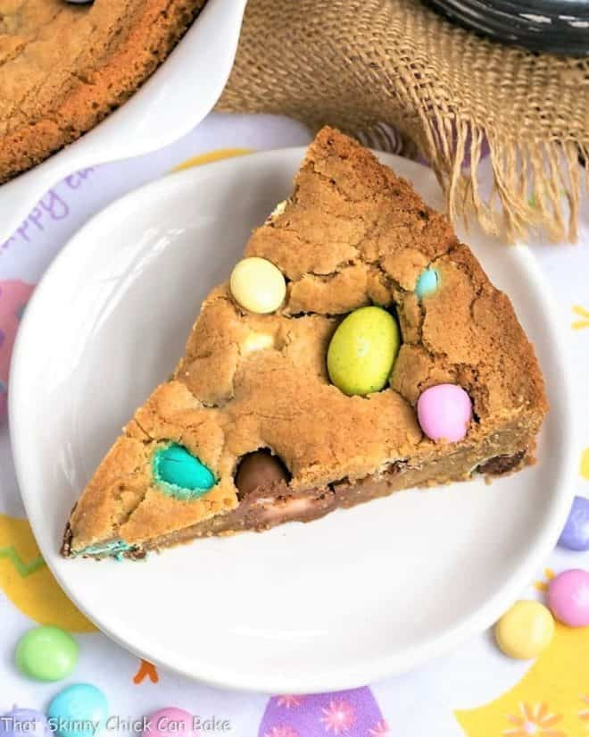 overhead image showing a slice of Easter cookie cake on a white dessert plate