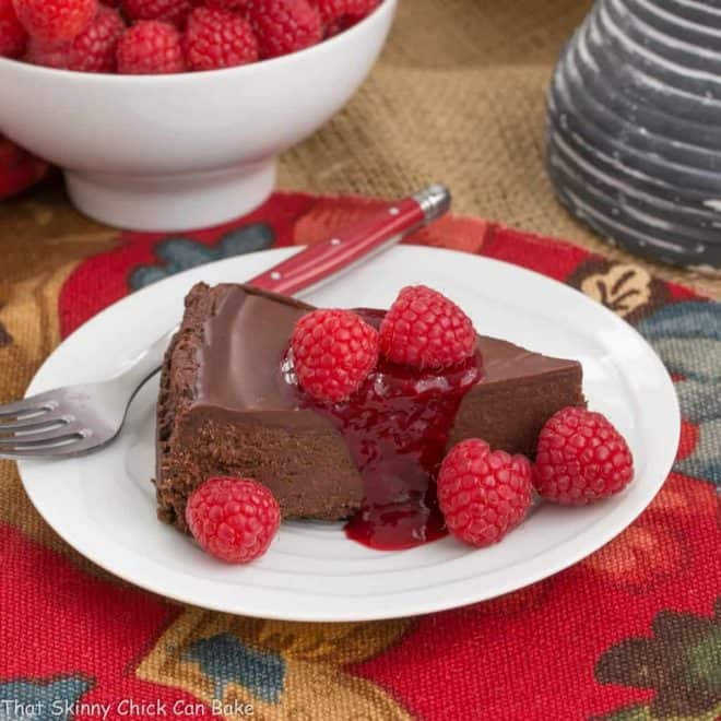 a slice of Flourless Chocolate Torte with Raspberry Sauce garnished with fresh raspberries