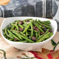 Side view of mustard green beans in a white serving bowl
