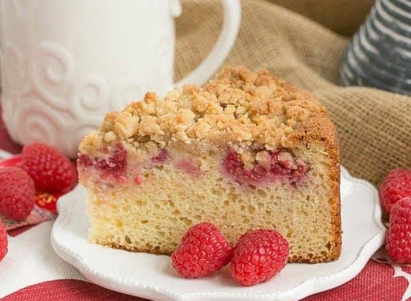 A piece of raspberry coffee cake on a white plate with two raspberries