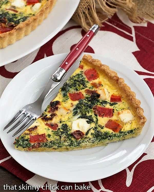 Sun-dried Tomato and Spinach Quiche slice on a white plate on a red and white napkin