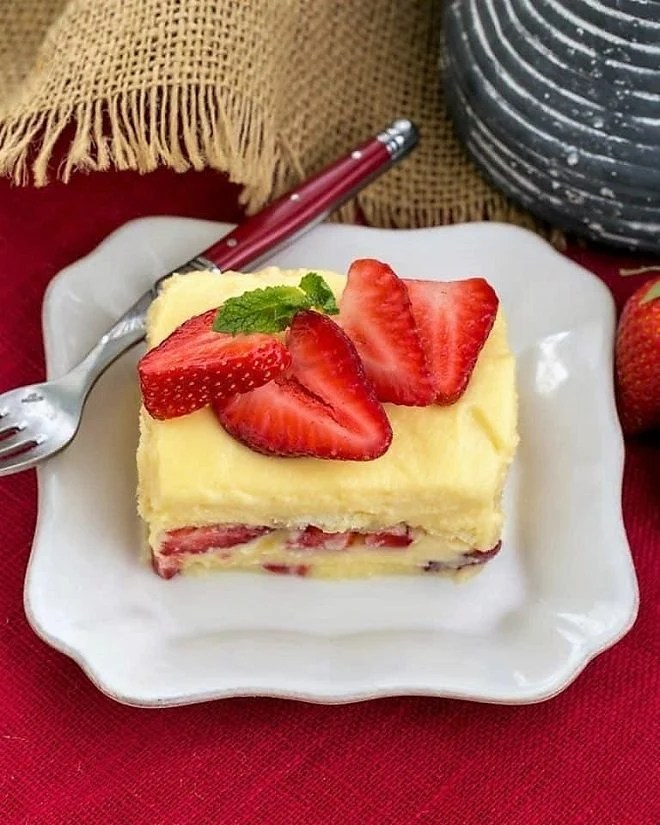 Berry Tiramisu with Grand Marnier garnished with fresh strawberries on a square white plate