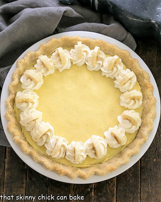 Overhead view of banana cream pie with whipped cream and banana slices to garnish