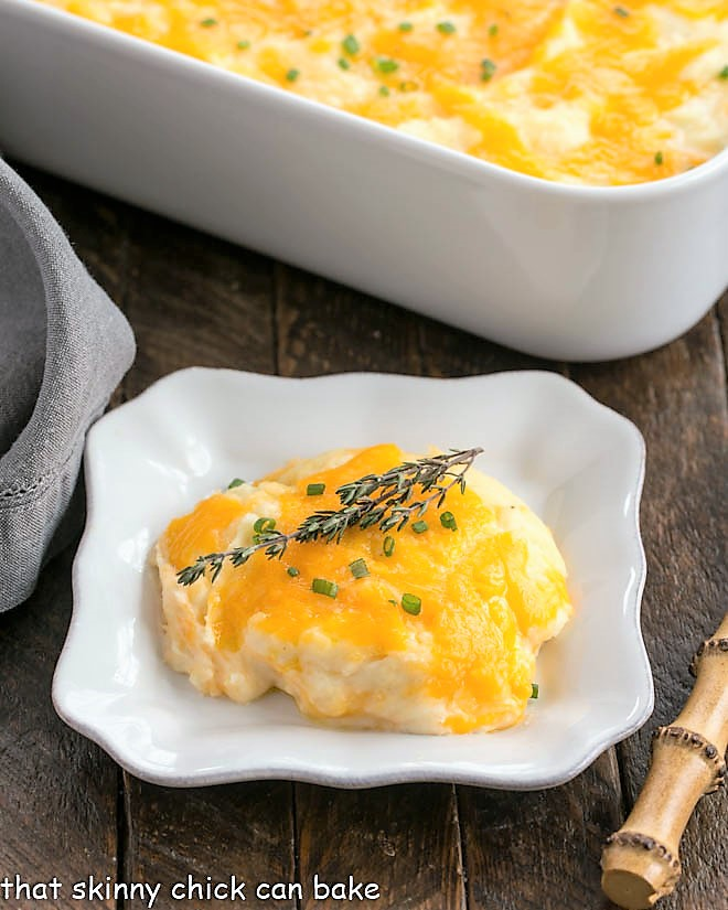 Cheesy Mashed Potato Casserole on a square plate with the casserole dish in the background