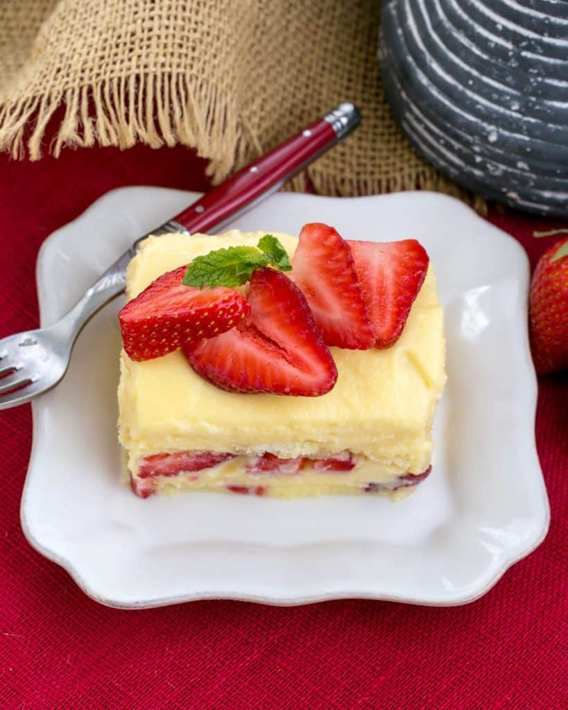 Berry Tiramisu with Grand Marnier slice on a square white plate with a red handled fork