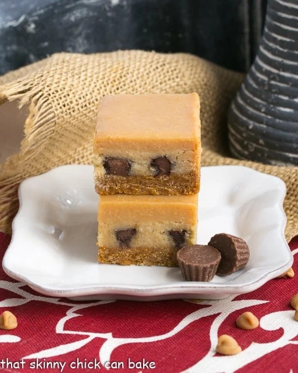 Peanut Butter Cheesecake Bars stacked on a square white dessert plate