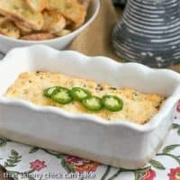 Jalapeno Popper Dip in a loaf pan topped with sliced jalapenos