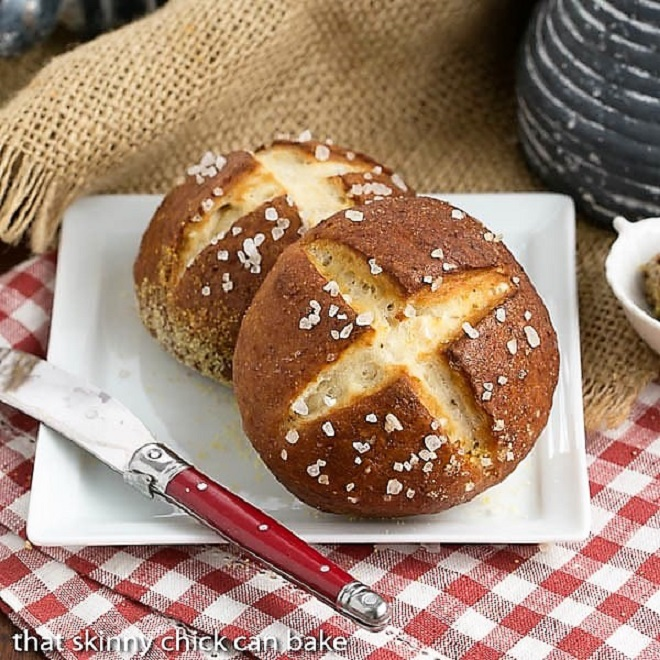 Two Pretzel Rolls on a square white plate with a red handled knife