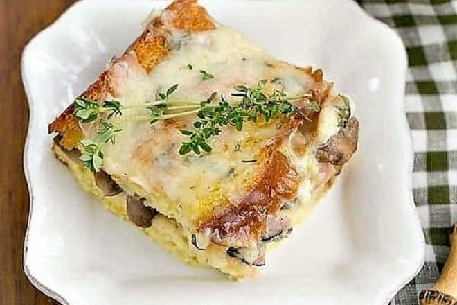 A slice of Ham and Mushroom Strata on a square white plate