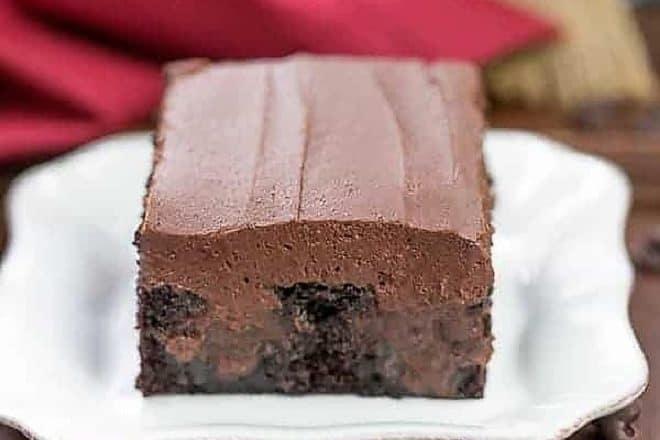 A slice of Triple Chocolate Poke Cake on a square white plate