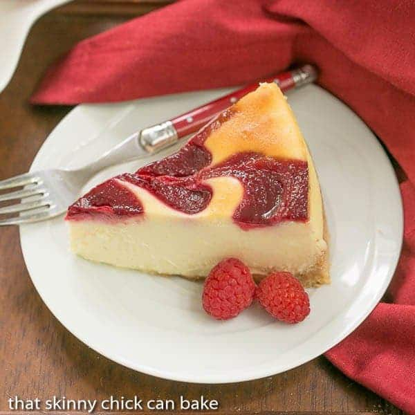 White Chocolate Raspberry Swirl Cheesecake slice on a white plate with fresh raspberries
