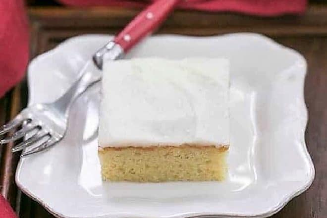 Slice of white sheet cake with a red handled fork