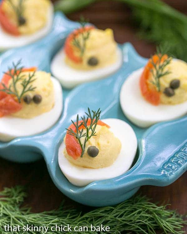 Smoked Salmon Deviled Eggs close up of garnished eggs in a blue ceramic egg dish