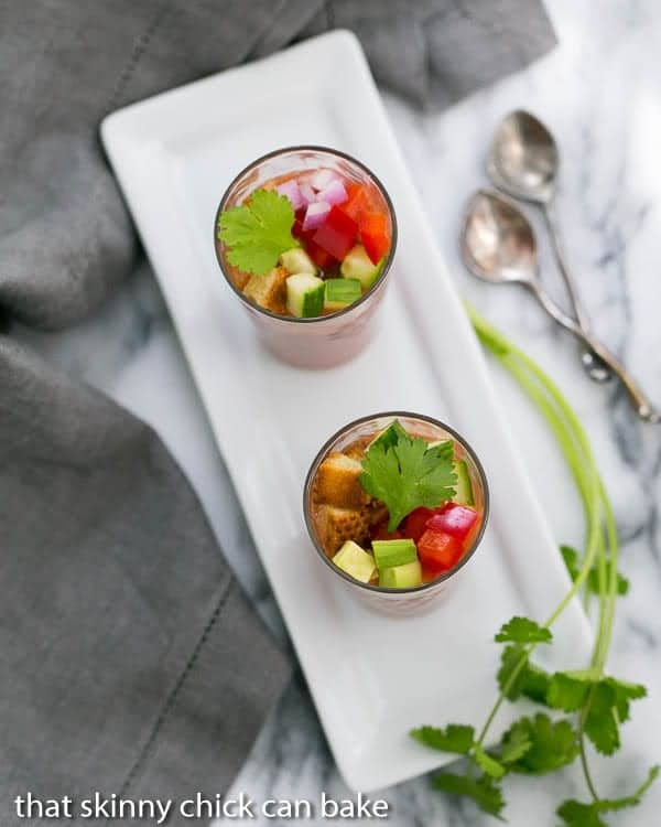 Gazpacho Shooters on a white rectangular tray with a sprig of cilantro