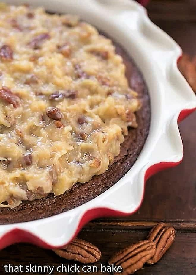 German Chocolate Brownie Pie in a ruffle edged pie plate with pecan halves