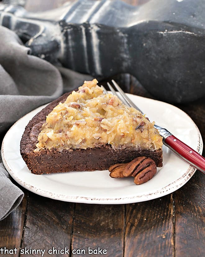 Slice of German Chocolate Brownie Pie on a round white plate with a red handled fork