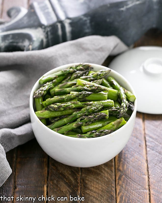 Oven roasted asparagus with balsamic brown butter in a white ceramic bowl