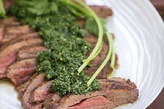 Close view of Grilled Flank Steak with Chimichurri Sauce on a white oval platter