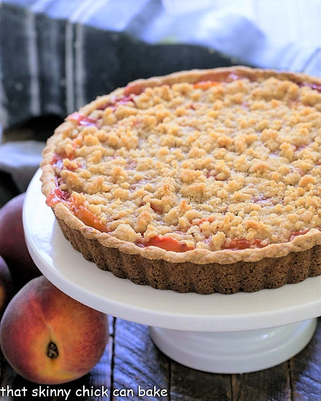 Streusel Topped Peach Tart on a white ceramic cake stand
