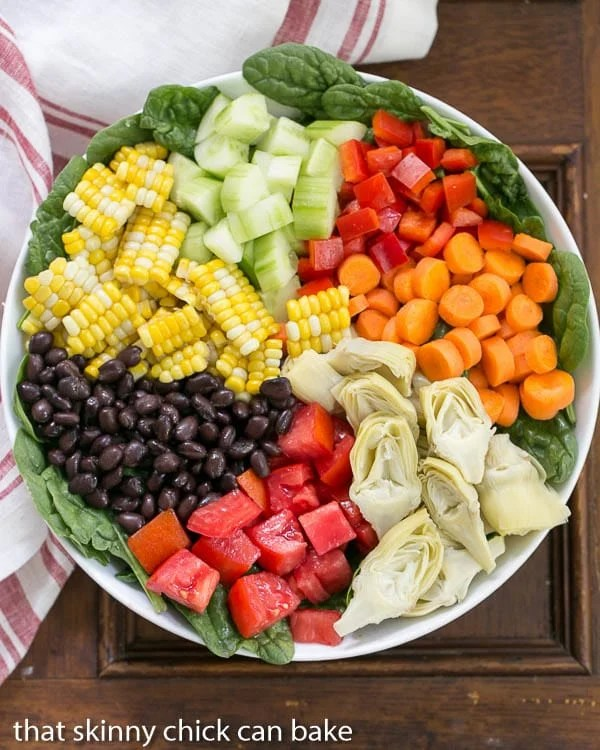 Overhead view of a composed Summer Vegetable Salad in a white bowl