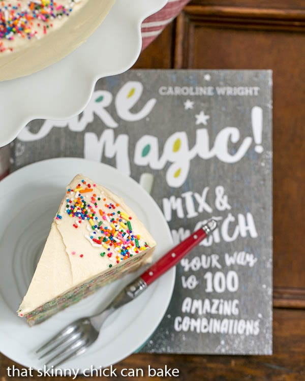 Slice of Festive Confetti Layer Cake sitting on top of a cookbook