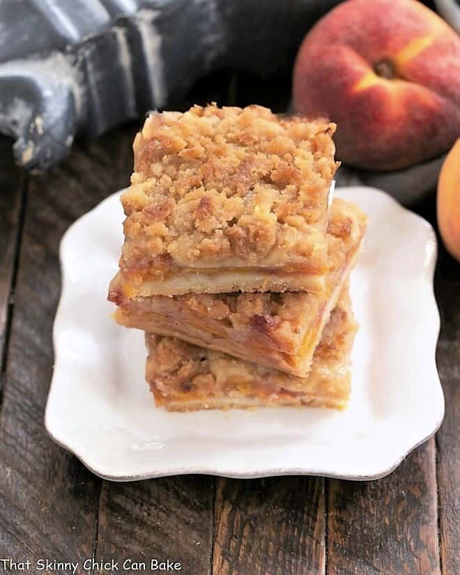 3 peach pie bars stacked on a square white plate