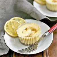 Two Lemon Curd Mini Cheesecakes on dessert plates with dried lemon slices