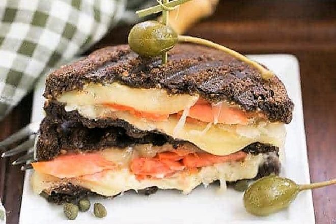 Smoked Salmon Reuben Sandwich cut in half and stacked on a white plate