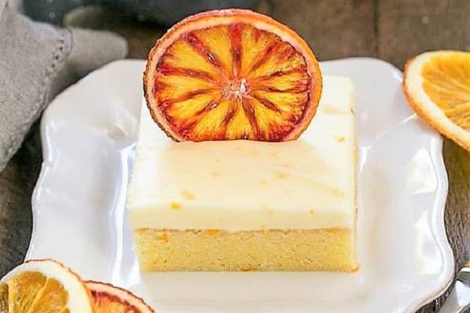 Orange Cake with Cream Cheese Frosting on a square white plate with dried orange slices