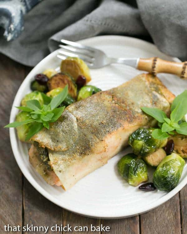 Potato Shingled Salmon on a white plate with brussels sprouts