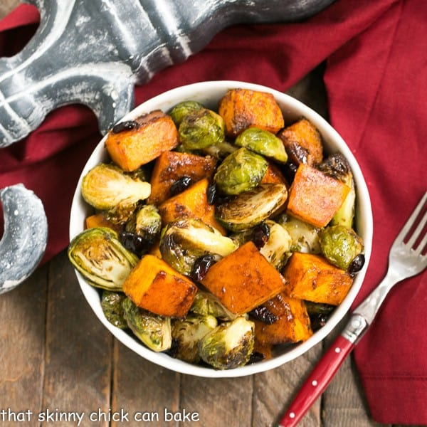 Overhead view of Roasted Autumn Vegetables in a white bowl with a red handled fork