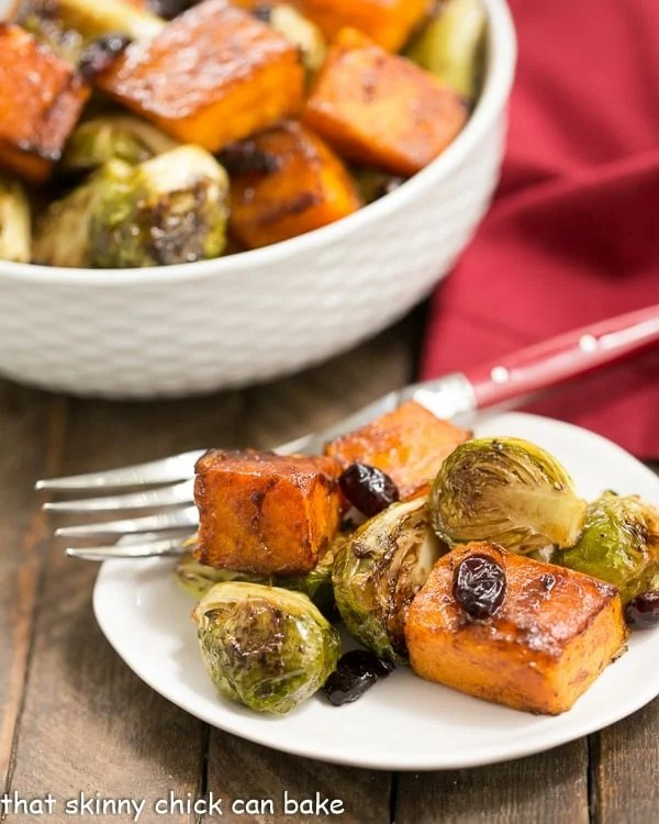 Roasted Autumn Vegetables on a small white plate with a bowl of roasted vegetables