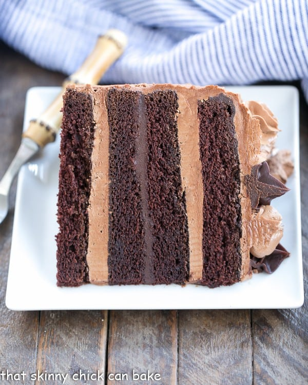 Chocolate Fudge Layer Cake slice on its side on a white square plate