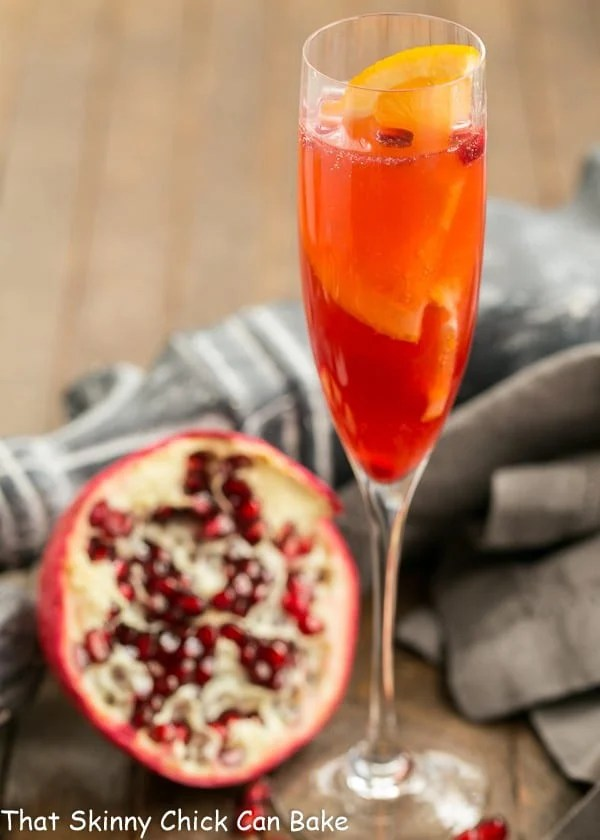 Pomegranate Champagne Cocktail in a champagne flute with a half pomegranate