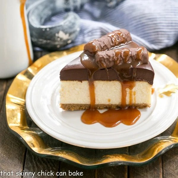 Twix Cheesecake on a white plate drizzled with caramel